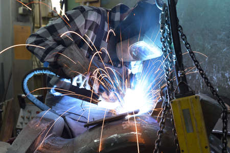 Photo pour Welder in protective clothing at the workplace in an industrial company in steel construction - image libre de droit