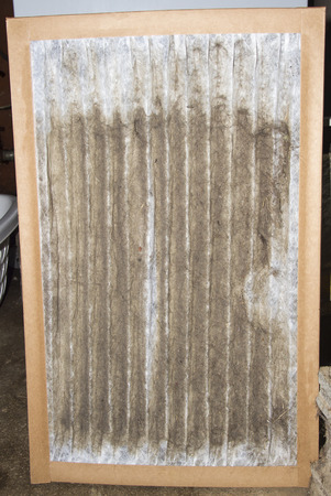 Front view of a dirty furnace filter taken out of a customers gas furnace.