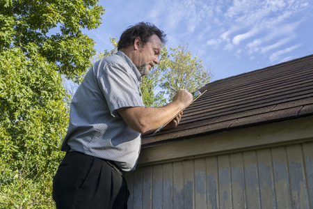 Insurance adjuster figuring hail damge done to insureds roof.