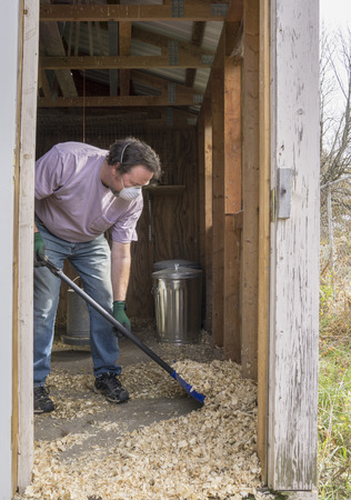 Chicken farmer cleaning a coop out to prevent Avian Flu and other diseases.