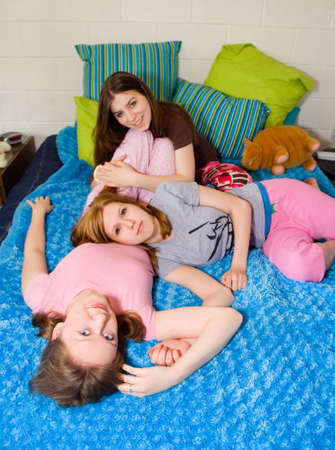 Young women wearing pink pajamas on a fuzzy blue blanket.