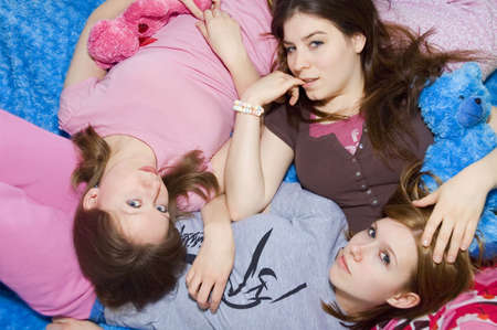 3 girls laying on each other in their pajamas.