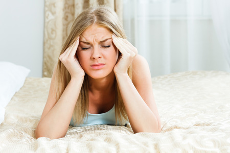 Woman is lying on her bed,she is having a headache