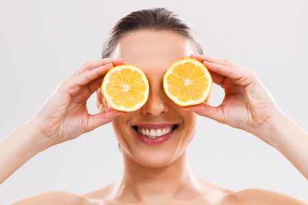 Beautiful woman is covering her eyes with slices of lemon.