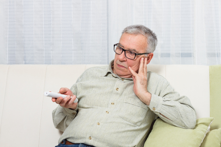 Senior man is trying to find something interesting on tv to pay his attention,but there is nothing interesting.
