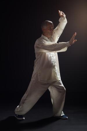 Foto de Senior man enjoys exercise Tai Chi indoor. - Imagen libre de derechos