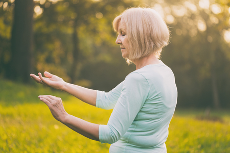 Photo pour Senior woman enjoys  exercise Tai Chi in the nature.Image is intentionally toned. - image libre de droit