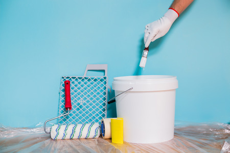 Photo pour Image of equipment for painting wall and man holding paintbrush. - image libre de droit