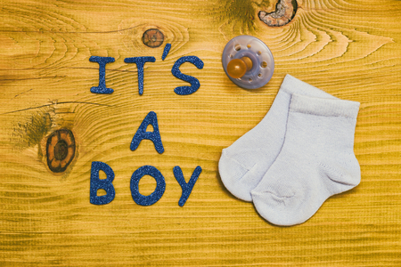 Photo pour Text it's a boy with pacifier and little baby socks on wooden table.Toned photo. - image libre de droit