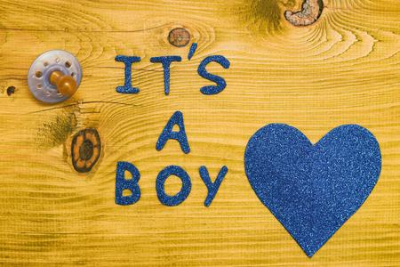 Photo pour Text it's a boy with pacifier  and heart shape on wooden table.Toned photo. - image libre de droit