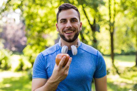 Photo pour Sporty man eating apple in the park. - image libre de droit
