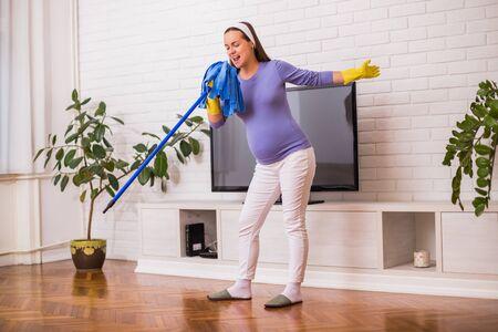 Photo pour Beautiful pregnant woman enjoys cleaning her house. - image libre de droit