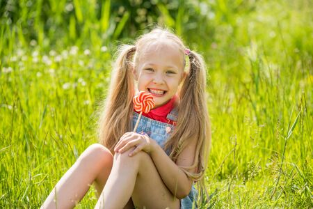 Photo pour Blonde little girl with long hair and candy on a stick - image libre de droit