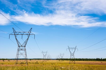 Photo pour Large electrical transmission towers and power lines receding into distance on rural fields under partly cloudy sky. - image libre de droit
