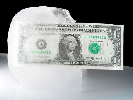 US paper currency (one dollar) in half frozen ice representing a current downsized economy, financial crisis, unemployment and investment lose.  Ice melting could also mean the economy is getting better, coming out from a prior frozen state.