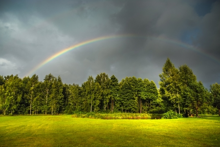 Real rainbow against a stormy sky a beatiful green countryside in summer
