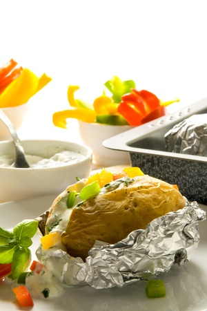 Baked potato with sour cream, herbs and pepper
