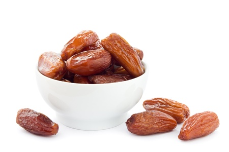 Dates in a white bowl on a white background