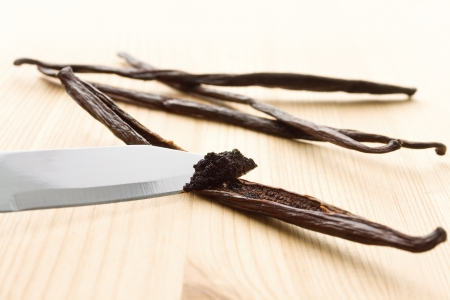 Vanilla mass being scratched out of vanilla beans with a knife