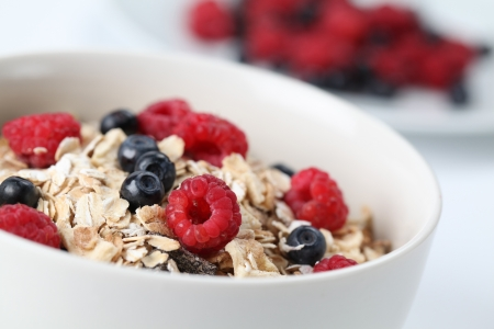 Granola with fresh organic raspberries and blueberries. Shallow DOF