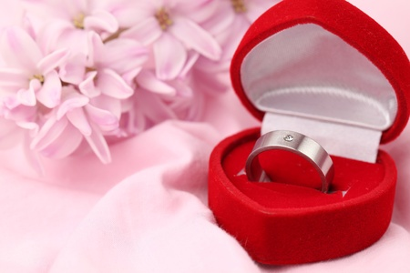 Photo for Titanium engagement ring with diamond in a heart shaped box on pink background with pink hyacinth. Shallow dof - Royalty Free Image