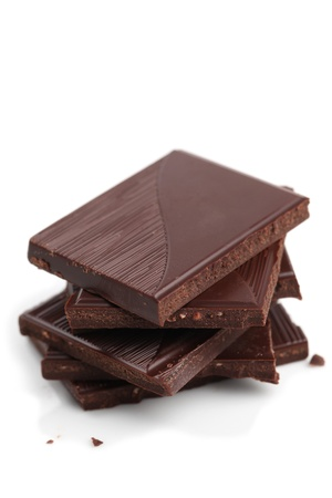 Stack of dark chocolate pieces on white background. Shallow dof