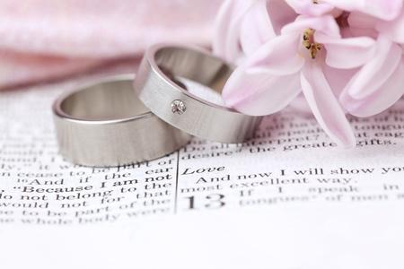 Foto de Titanium wedding rings on the Bible open to 1st Corinthians 13, a passage about love  Shallow dof - Imagen libre de derechos