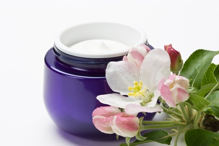 Cosmetic moisturizing cream for face skin with flower in plastic container