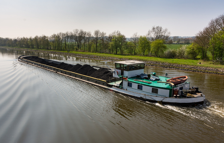 Cargo ship loaded with coal on the canal in Wesermarsch near Balge