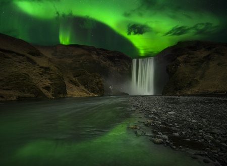 Flash of Aurora polaris above skogafoss waterfall, iceland