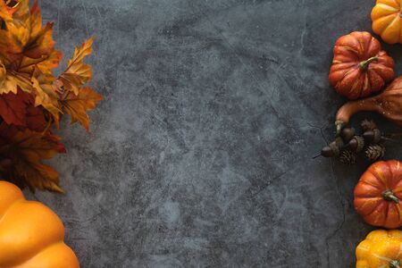Foto de Thanksgiving background with pumpkins, leaves and nuts on a grey cement background. - Imagen libre de derechos