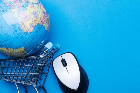 Shopping cart on a blue background with computer mouse and globe