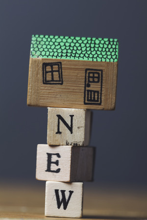 House model with cost word made from wooden blocks. Home finance concept