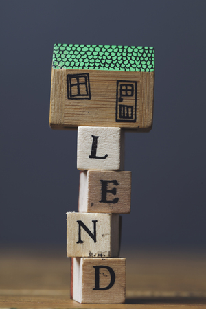 Home lending concept. House model with lend word made from wooden blocks.