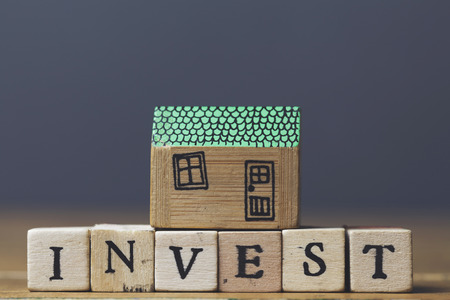 Home investment concept. House model with invest word made from wooden blocks.