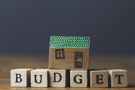 Home budget concept. House model with budget word made from wooden blocks.