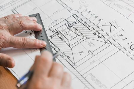 Photo pour Male hand with pen in drawing. Blueprints of equipment drawings. Paper Draft or Technical Diagram of Mechanic Tool for Metalwork Job. Drawing project in pencil on sheet of close-up. - image libre de droit