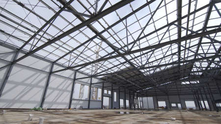 Photo pour Construction of modern factory or warehouse, modern industrial exterior, panoramic view. Modern storehouse construction site, structural steel structure of new commercial building - image libre de droit