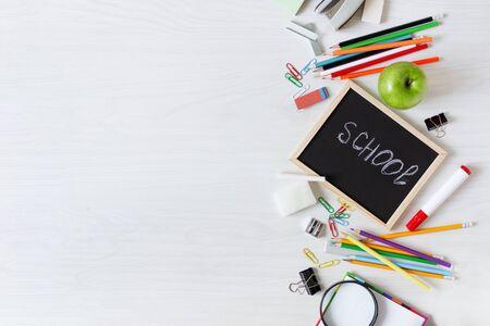 Foto de School supplies on white wooden table top view. Stationery. Back to school concept. - Imagen libre de derechos
