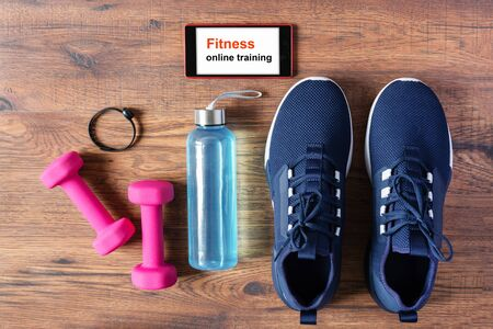 Photo pour Fitness equipment, sport shoes and smartphone on wooden background top view. App for sport training indoors. Online Fitness training concept. Online workout staying at home. - image libre de droit