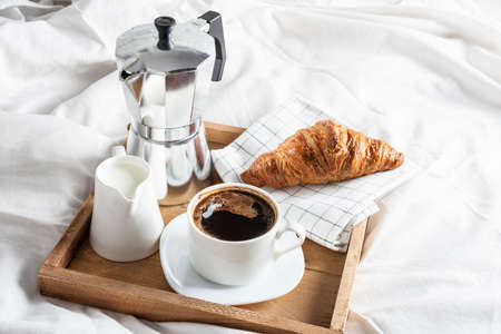 Photo pour Wooden tray with cup of black coffee, jug of milk and croissant on white linen bed. Breakfast in bed with coffee and croissants. - image libre de droit