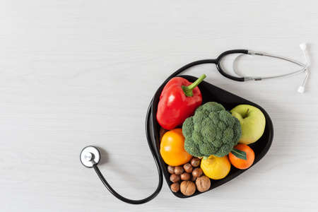 Photo pour Heart shaped bowl with vegetables, fruits, nuts and stethoscope on white wooden background top view. Healthy eating concept. - image libre de droit