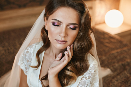 Photo for Beautiful brown-haired woman with wedding hairstyle and bright makeup sits with closed eyes on the bed - Royalty Free Image