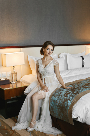Foto de Beautiful brunette woman, with wedding hairstyle and perfect body with sexy long legs, in stylish peignoir and in lace lingerie posing on the bed in luxury interior - Imagen libre de derechos