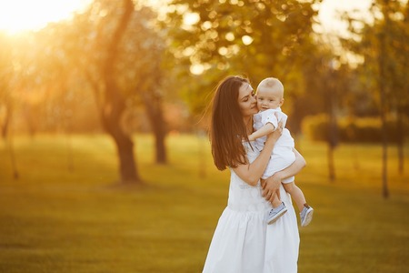 Photo for Beautiful young woman in a long white dress with a cute little baby boy in shirt and shorts on her hands posing at the green garden in sunny summer day - Royalty Free Image