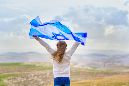 Little patriot jewish girl standing and enjoying with the flag of Israel on blue sky background.Memorial day-Yom Hazikaron, Patriotic holiday Independence day Israel - Yom Haatzmaut concept