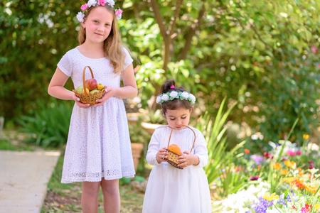 Foto für Harvest. Shavuot. Two cute smiling little girls holds basket with fruits at the beautiful summer garden. Portrait adorable small kids outdoor. - Lizenzfreies Bild