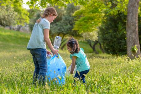 Photo for Little girls takings plastic bottles from grass. Children picking up litter in the park . - Royalty Free Image