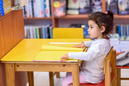 Photo pour Little Girl Indoors In Front Of Books. Cute Young Toddler Sitting On A Chair Near Table and Reading Book. Child reads in a bookstore, surrounded by colorful books. Library, Shop, Shelving In Home. - image libre de droit