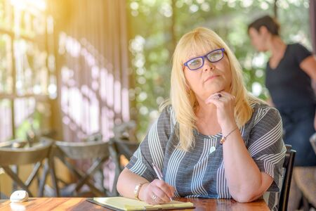 Foto de Portrait of beautiful plus size middle age woman working and making notes to her diary on sunny terrace of cafe. Elegant middle aged lady posing with modern glasses. - Imagen libre de derechos